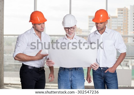 Grey-headed architect is holding a blueprint and looking at it seriously. He is explaining to his young colleagues the concepts of building. The workers are listening to his attentively - stock photo