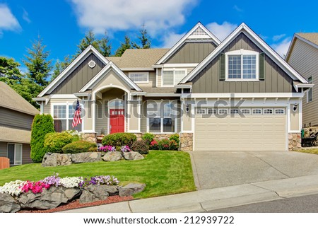 Grey house exterior with entrance porch and red door. Beautiful front yard landscape with vivid flower and stones - stock photo