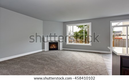 Grey house interior of living room with fireplace and carpet floor. Windows overlooking back yard.