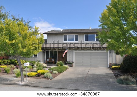 Grey house with flag flying, bench in front and white mailbox near street - stock photo