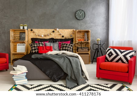 Grey interior with red armchairs, big bed, pattern carpet and pillow