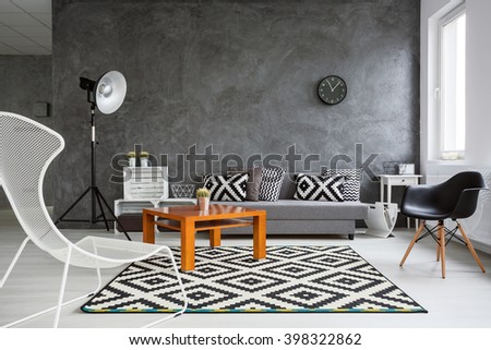 Grey interior with sofa, chairs, standing lamp, small wood table and black and white pattern decorative elements - stock photo