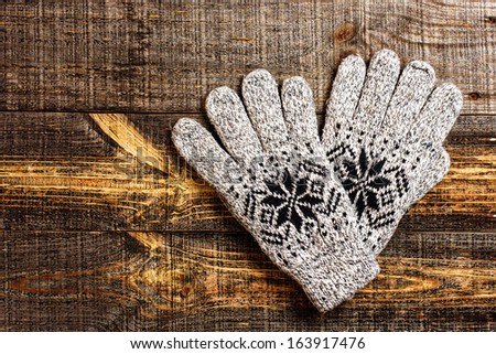 Grey knitted winter gloves isolated on wooden boards  - stock photo