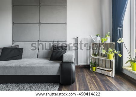 Grey living room with sofa, decorative cement wall tiles and DIY stand shelf  - stock photo
