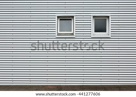 Grey meatal wall with windows - stock photo