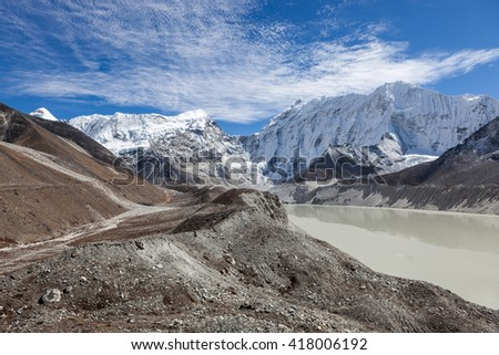 Grey moraine lake and snowy mountain peak in Himalayas, Nepal. Mirror water surface of a big moraine lake. Imja Tsho moraine lake at the foot of the Imja Glacier and Amphu Lapcha pass. - stock photo