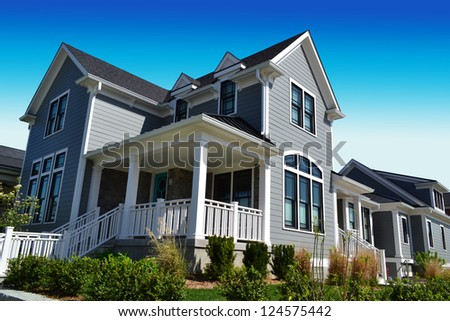 Grey New England Style Suburban Dream Home with Large Front Porch - stock photo