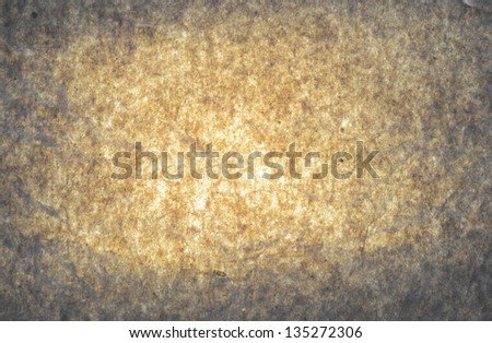 Grey paper with brown yellow glow spot in the middle. - stock photo