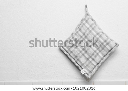 grey pot holder hanging on nail isolated background oven mitt
