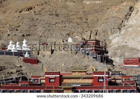 Grey-red-white painted buildings on grounds of the 1073 AD founded North Seat of the Sakya-Grey Soil monastery. Ponpori Hill over the right bank of Trum or Chong Chu-river. Sakya-Shigatse pref.-Tibet. - stock photo