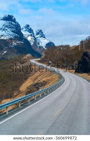 Grey road in Norvegian snowbound mountains - stock photo