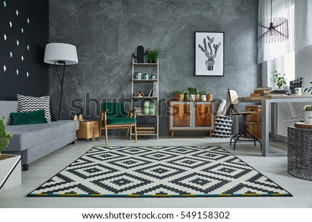 Grey room with pattern carpet and wooden furniture