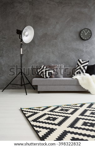 Grey room with sofa, new standing lamp, and pattern decorations in black and white  - stock photo