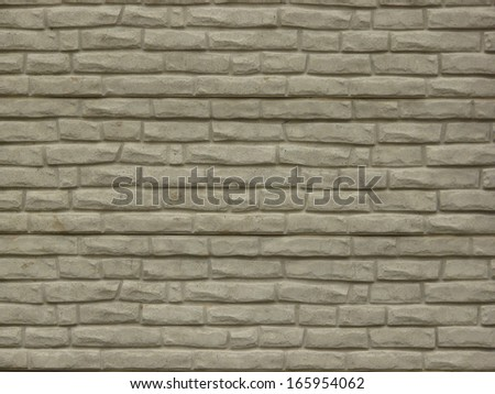 Grey rough stone set consistently in linear fashion but jutting out irregularly.