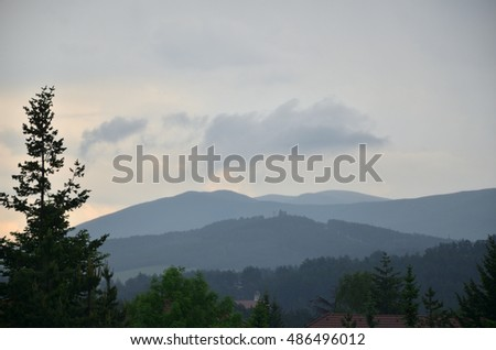 Grey sky with clouds over mountain hills bringing stormy weather in late afternoon