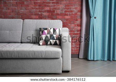 Grey sofa against brick wall in the room - stock photo