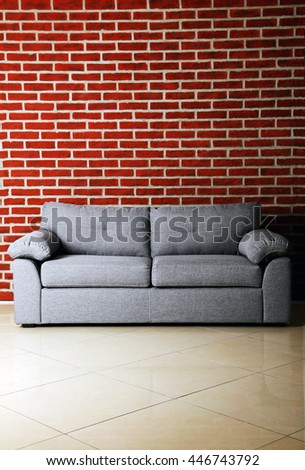 Grey sofa on a red brick wall background - stock photo