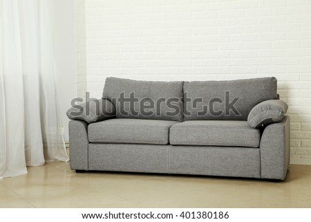 Grey sofa on a white brick wall background - stock photo