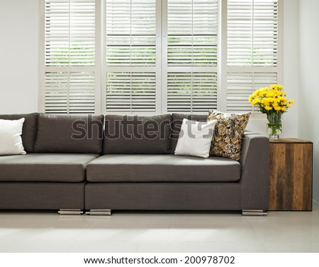 Grey sofa with pillows in front of lovered windows  - stock photo
