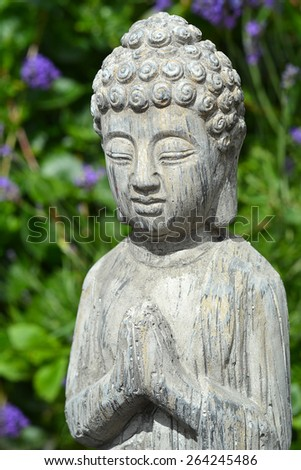 Grey stone buddha statue in lavender garden, with hands together and closet eyes.