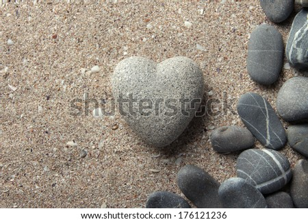 Grey stone in shape of heart, on sand background - stock photo