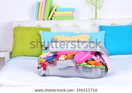 Grey suitcase with clothing on bed close-up - stock photo