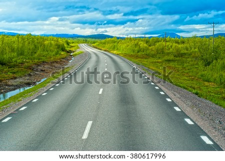 Grey sweden road to Norvegian mountains in sunny summer day - stock photo
