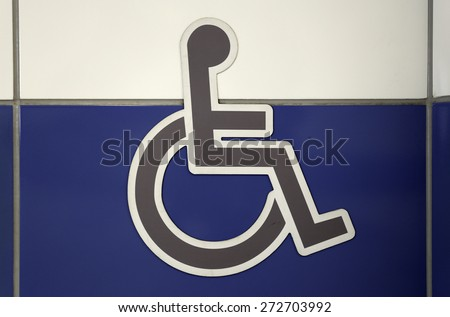 Grey wheelchair sign on the white and blue wall. Public restroom signs with a disabled access symbol. - stock photo