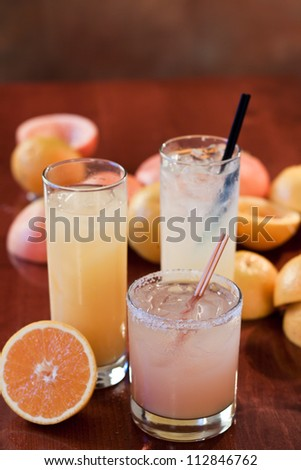 Greyhound, salty dog, screwdrivers made with fresh fruit on a wooden bar top - stock photo
