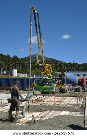 GREYMOUTH, NEW ZEALAND, FEBRUARY 2, 2014: Builder uses a concrete pump to direct wet concrete into the foundations of a large building near Greymouth, South Island, New Zealand, February 2, 2014