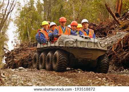 GREYMOUTH, NEW ZEALAND, 23-12-2013: Unidentified men travel in an all terrain vehicle while working in the bush on the West Coast of New Zealand
