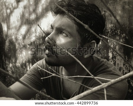 Greyscale image of a young man looks far against a grunge background