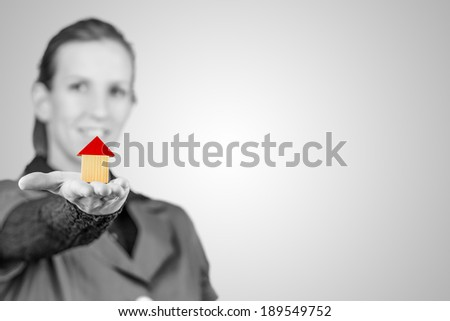 Greyscale image with selective coloring of a smiling young woman holding out a model house on the palm of her hand conceptual of goals, ownership, investment, risk and real estate, copyspace. - stock photo
