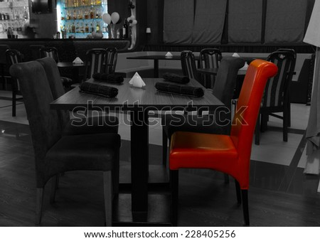Greyscale restaurant interior with a single red chair in selective color at the table in the foreground - stock photo