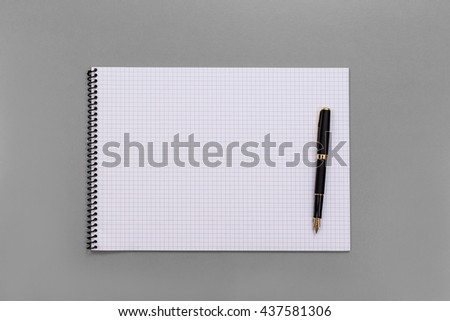 Grid book notepad and luxury fountain pen display on business table, high angle view or top view grid paper notebook and pen on grey table with copy space.