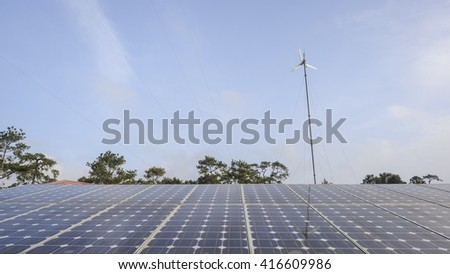 Grid solar panels and wind turbine with blue sky in countryside.