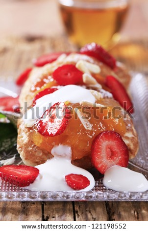 Griddle cakes topped with fruit preserves and sliced strawberries - stock photo