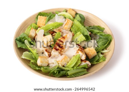 Griddled chicken caesar salad on white background - stock photo