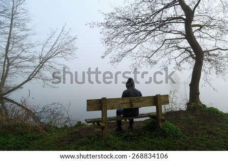 Grief concept: depressed man sitting on a bench at a lake during a foggy morning. - stock photo