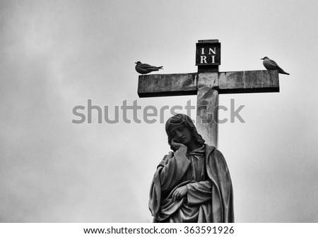 Grieving Virgin Mary statue (Charles Bridge in Prague). Artistic film grain. - stock photo
