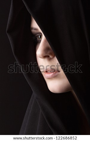 Grieving young woman in a black dress on a black background - stock photo