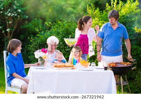 Grill barbecue backyard party. Happy big family, mother, father, teen son, cute toddler daughter and little baby, enjoying BBQ lunch with grandmother eating meat in the garden with salad and bread.  - stock photo