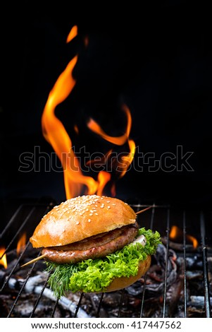Grill concept.Hamburger with roll sausage on grill with flare on background. - stock photo