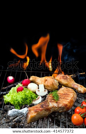 grill concept with flame.  Assorted delicious grilled meat with vegetable over the coals on a barbecue - stock photo