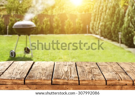 grill in garden and wooden table place and sun light and trees in garden  - stock photo