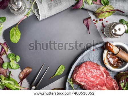 Grill steak ingredients around  blank chalkboard. Grill or BBQ steak marinating with Barbecue sauce and basting brush on stone table background, top view. - stock photo