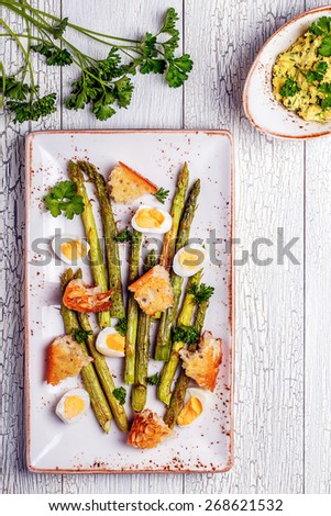 Grilled asparagus with quail eggs on a white wooden background