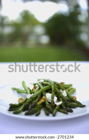 Grilled Asparagus with walnuts and goat cheese on a white plate - stock photo