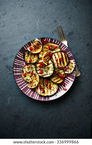 Grilled aubergine marinated in olive oil with ramsons and pomegranate seeds - stock photo