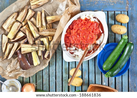 Grilled aubergines and raw vegetables for cooking a meal - stock photo